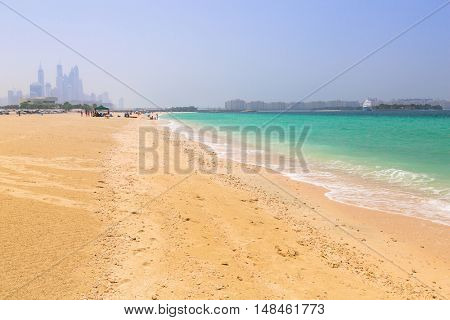 DUBAI, UAE - 1 APRIL 2014: People on the Jumeirah Beach in Dubai, UAE. Jumeirah Beach is a white sand beach that is located and named after the Jumeirah district of Dubai.