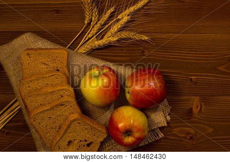 Ripe apple square pieces of bread and ears on sacking on a wooden table