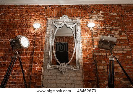 Old ornate frames on mirror glas hanging on a brick wall.
