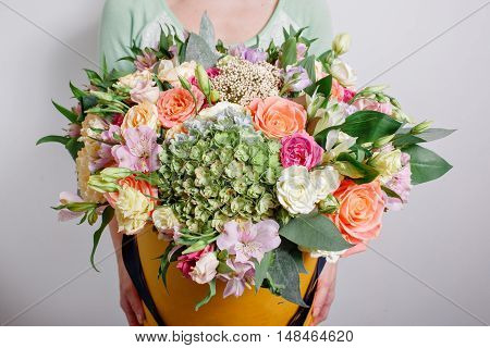 rich bouquet with hydrangea in woman hand . colorful roses and various color mix flowers.