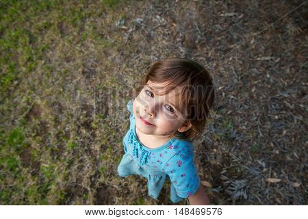 A cute little girl looks up at the camera with a smirk. She is surrounded with a lot of copy space filled with grass and dead leaves.