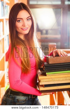 Education highschool concept. Lovely female student fashion long hair girl in college library with stack books.