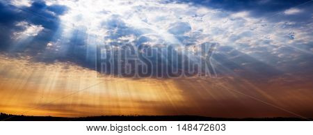 Amazing dramatic sunset with sunbeams shining through the clouds over a silhouetted city