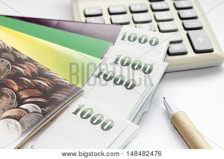 Concept of savings : Money, calculator, pen and savings account passbook on white background