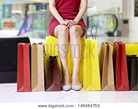 young female woman shopper with beautiful legs surrounded by colorful shopping bags resting in mall or department store