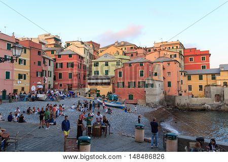 Genoa, Italy - June 25, 2016: Bay with restaurants and bars and Mediterranean Sea in Boccadasse. Boccadasse is an old mariners neighbourhood of Genoa and is a tourist attraction.