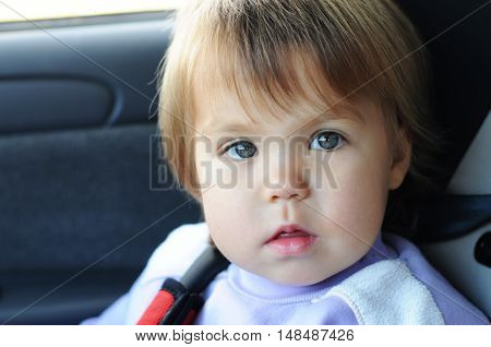 Little girl portrait in automobile belted in child safety seat