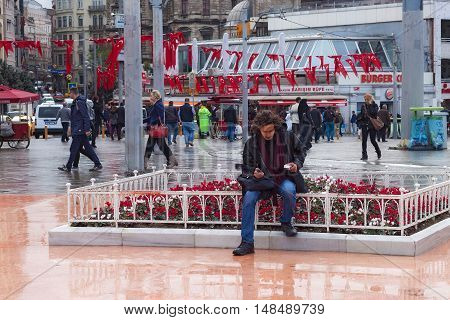 TURKEY ISTANBUL - NOVEMBER 06 2013: Unknown young man resting on the Taksim Square. Taksim is a main transportation hub and popular destination tourists. And a favourite location for public events.