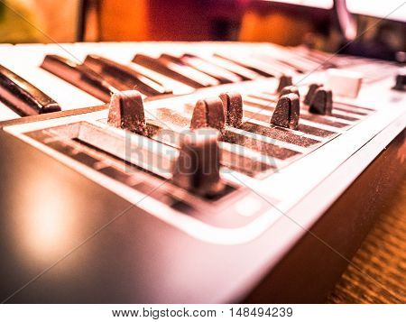 Keyboard of a synthesizer with sliders. Closeup of musical equipment .