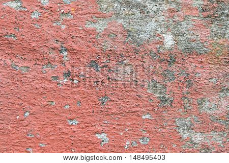 Closeup of chipped paint on old red wall