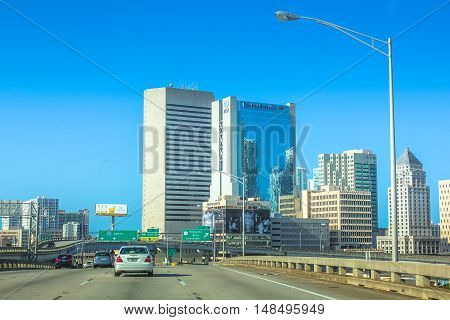 Miami, Florida, United States - April 8, 2012: cars driving on Miami Highway in the direction of 95 North Miami. Downtown Miami skyline in the background.