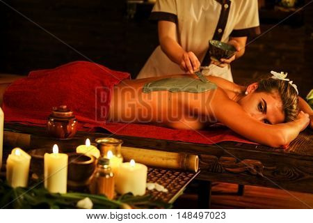 Young woman lying on wooden spa bed. Back massage with clay full body mask in spa salon. Girl on candles background in massage spa salon.