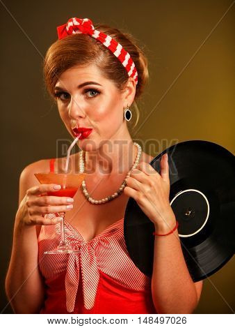 Girl in pin-up style keeps vinyl record and drink martini cocktail . Pin-up retro female style. Girl pin-up style wearing red dress. Girl has pin-up hair style.