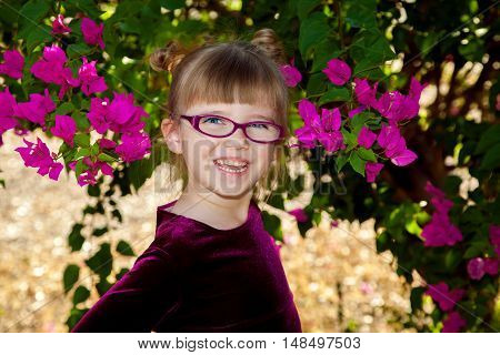 An adorable young girl with glasses and big blue eyes smiles with an open mouth for a portrait. She has two twisty buns in her hair and is in front of a bougainvillea plant.