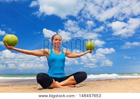 Fit woman exercising with young coconut on ocean beach. Sportive woman doing workout. Fitness woman summer vacation sport camp. Active sport lifestyle healthy nutrition natural diet for loss weight.