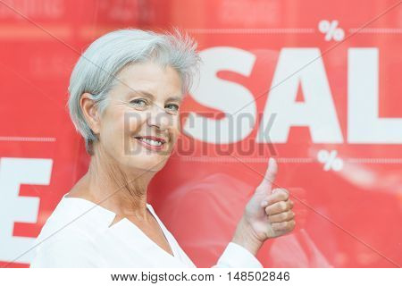 Senior woman in front of a sale sign