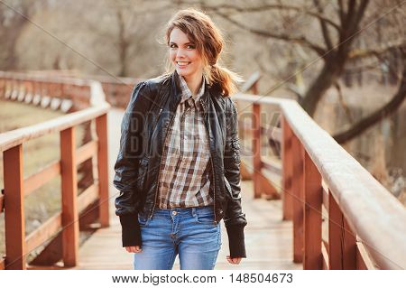 autumn outdoor portrait of young beautiful woman with natural makeup in leather jacket and plaid shirt soft vintage toned