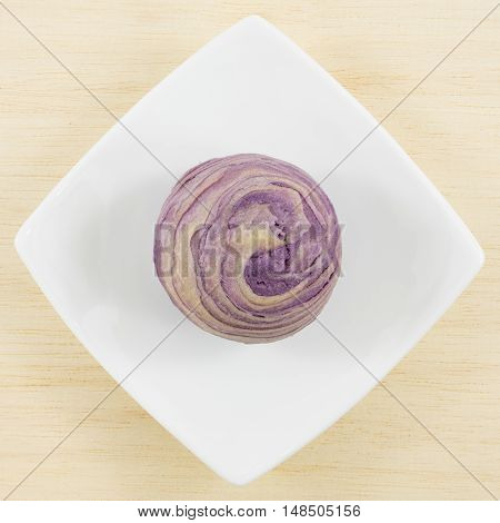 The Taiwanese violet crystal taro cake on the small white square dish.