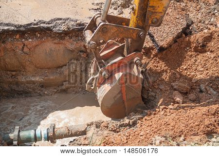 Excavator bulldozer work a hole the repair of pipe water and sewerage on road
