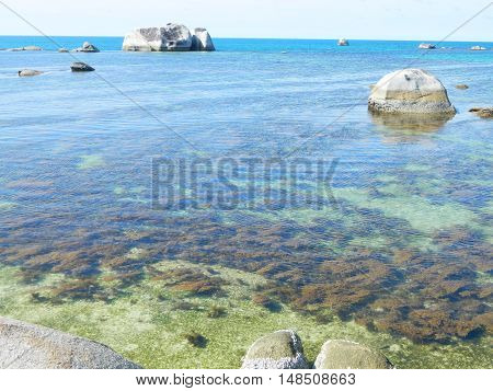 one side of the Tanjung Kelayang beach at Belitong Island, Very clear water so we can see the alga under the water. very beautiful scene, with big rocks.