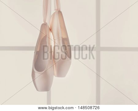 Pastel pink ballet shoes background. New pointe shoes with satin ribbon hanging on window, high-key soft toning with copy space