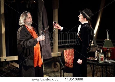 RUSSIA, MOSCOW - APR 15, 2015: Two actors are drinking alcohol beverages and playing his characters for performance (Kosmos) at drama theatre Modern.