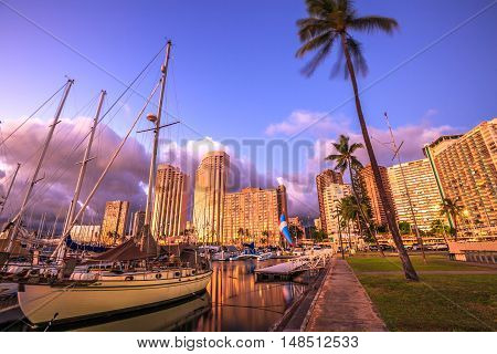 Beautiful panorama of sailing boats docked at the Ala Wai Harbor the largest yacht harbor of Hawaii and Honolulu skyline at twilight. On background, a luxurious hotel near Waikiki beach in Honolulu.
