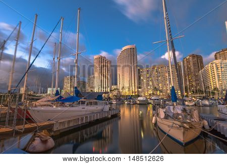 Beautiful panorama of sailing boats docked at the Ala Wai Harbor the largest yacht harbor of Hawaii and Honolulu skyline at sunset. On background, a luxurious hotel near Waikiki Beach.