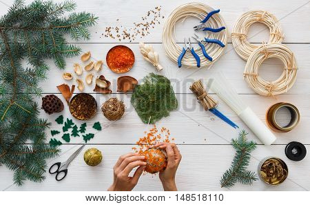 Creative diy craft hobby. Making handmade craft christmas tree ornaments, garland and balls. Home leisure, tools and trinkets for holiday decorations. Top view of white wood table with female hands.