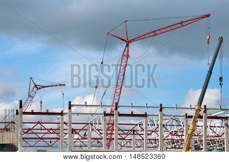 The process of of erection of a frame-span building. Monolithic concrete columns metal girders and cranes against the blue sky.