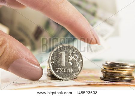 Hand takes the ruble against the background of dollars and banks with rubles