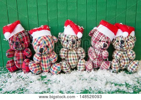 Little teddybears with red Santa Claus hats on Green