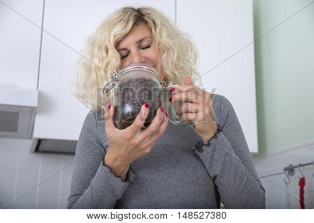 Blonde girl with curly hair is smelling coffee beans