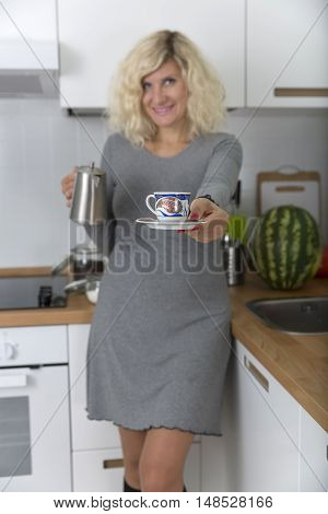 Blonde girl with curly hair is offering small cup of coffee