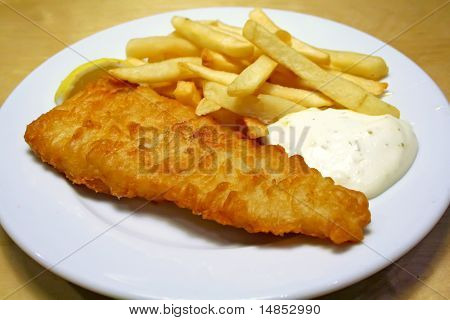 Fish and chips on a white plate with tartar sauce