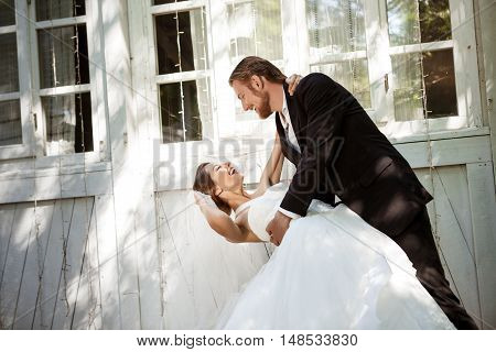 Young beautiful dressy newlyweds smiling, dancing outdoors. Copy space.