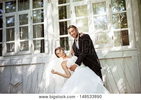 Young beautiful dressy newlyweds smiling, fooling, dancing outdoors. Copy space