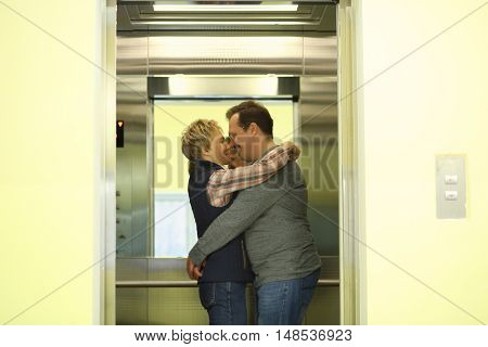 Man and woman hugging in the elevator