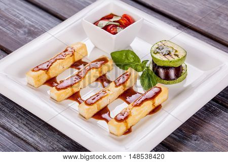 cheese sticks with sauce and vegetables on white plate