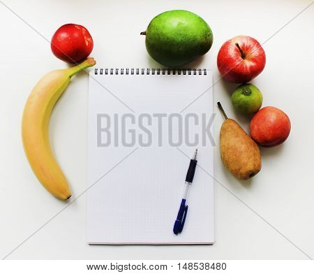 Notebook planner with blank empty page pen and colorful organic fresh fruits apple banana pear peach mango isolated on white table background Diet fitness planning, healthy eating food nutrition lifestyle concept with copy space close up