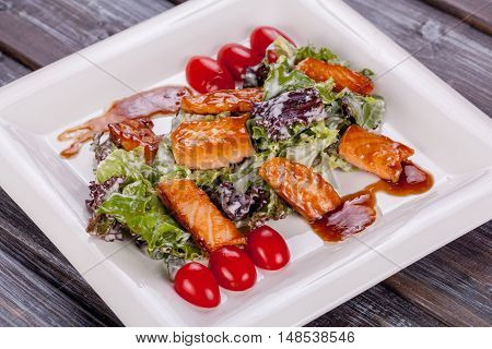 salad salmon fish in smoked sauce on wood background