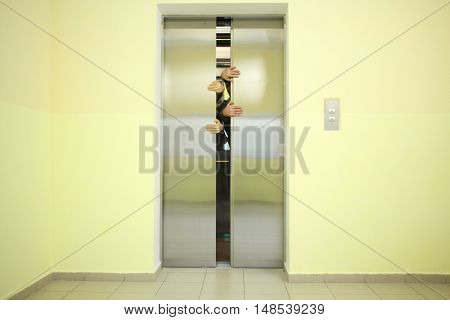Two pairs of hands sticking out of the elevator door