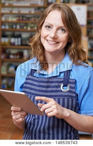 Portrait Of Delicatessen Owner With Digital Tablet