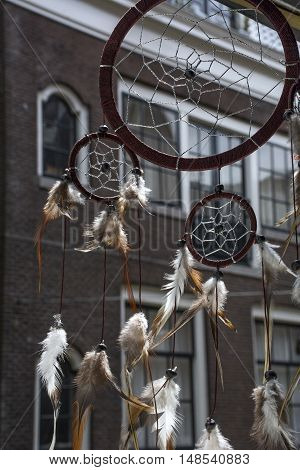 Brown dream catcher on the window with brown house as background