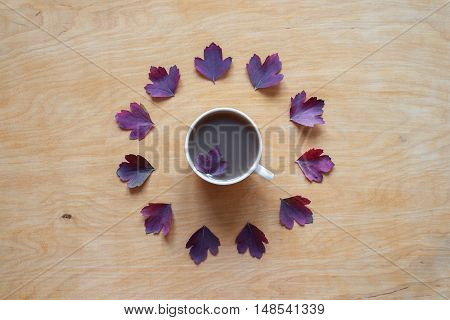 Cup of coffee and autumn leaves placed in a circle on a wooden background. Shot from above.