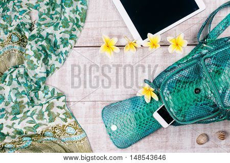 Ladies Fashion Accessories. Luxury handmade snakeskin (python) backpack, smartphone, tablet, many plumeria/frangipani flowers. Top view, flat lay, light wooden background. Free/empty space for text.