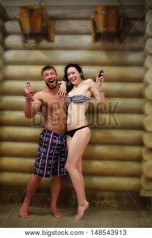 Barefoot man and a woman in a swimsuit standing under bucket-waterfall near log wall in a sauna