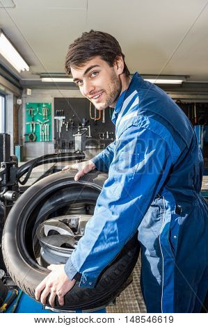 Portrait of confident male mechanic mounting car tire on rim in garage