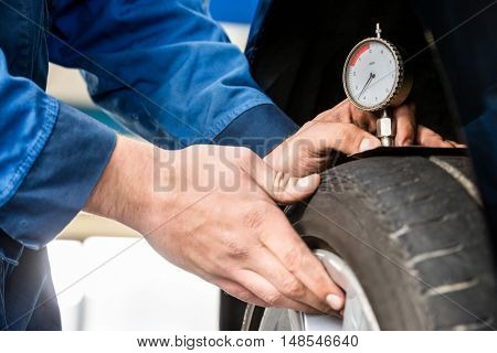Hands of male mechanic pressing gauge into tire tread to measure its depth at garage