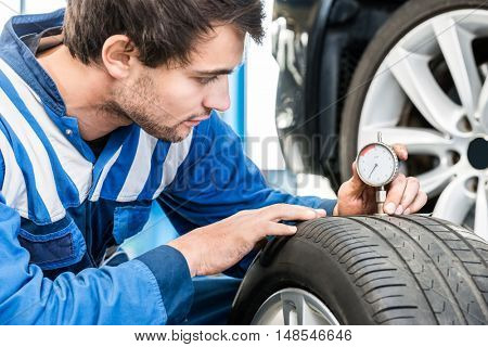 Young male mechanic pressing gauge into tire tread to measure its depth at garage